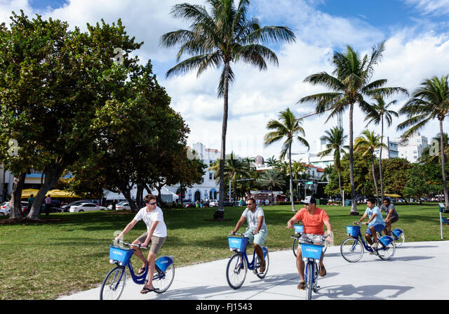 Miami Beach Florida Lummus Park Serpentine Trail Citibike station bike share program man riders riding bicycles - Stock Image