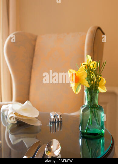 flower bouquet daffodils vase table setting flatware dining room spring yellow meal napkin chair - Stock Image