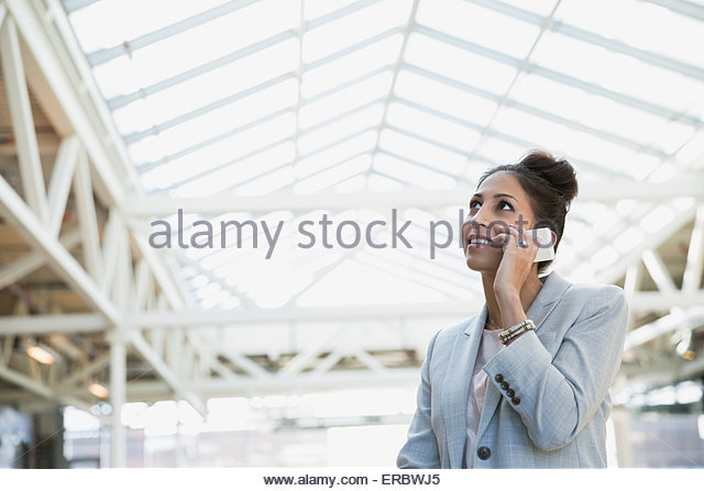 Businesswoman talking on cell phone and looking up - Stock Image