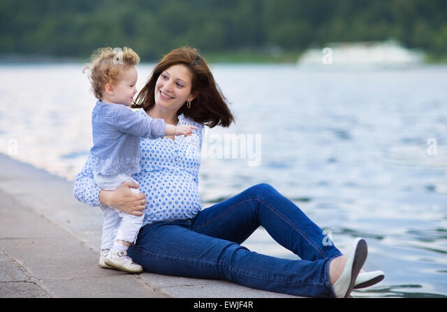 Young pregnant mother and her little baby daughter relaxing at a river bank in a city center - Stock Image