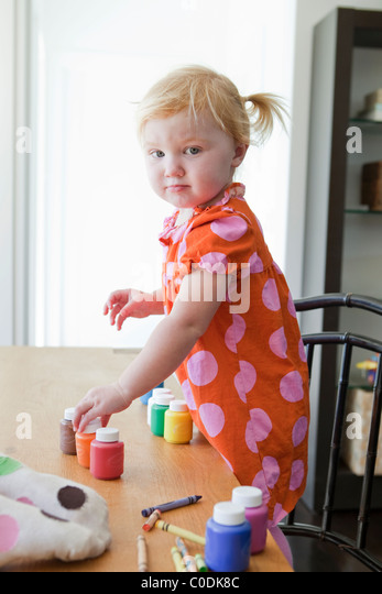 Little girl playing with bottles of paint - Stock Image