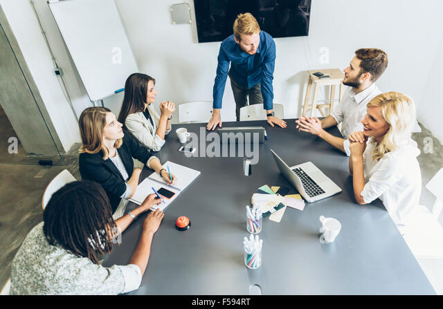 Office brainstorming, people sitting at desk - Stock Image