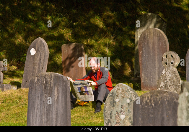 Man reading newspaper in cemetery graveyard flanked by headstones, ambleside lake district national park UK - Stock Image