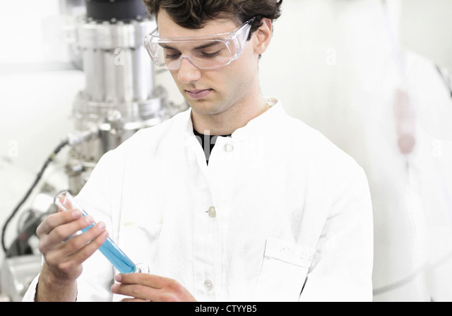 Scientist examining test tube in lab - Stock Image