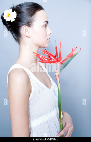 young woman with bird of paradise flower - Stock Image