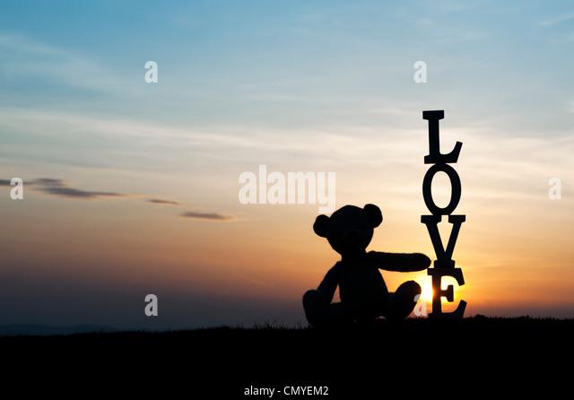 Teddy bear sitting next too the word LOVE at sunset. Silhouette - Stock-Bilder