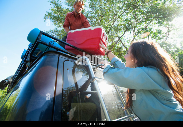 A couple loads a cooler onto a van in Florida. - Stock Image