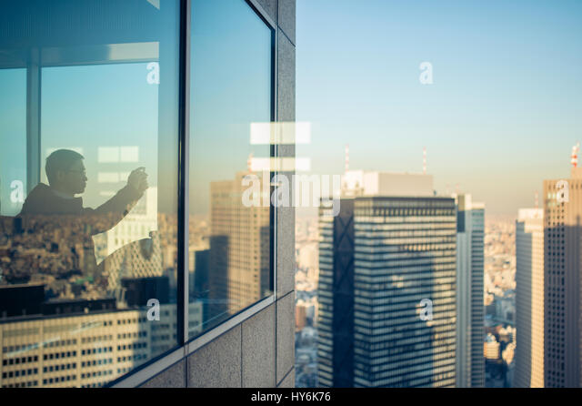 TOKYO  - JAPAN - JANUARY 11, 2017 A man is taking a photo of the view from the top of the Tokyo Metropolitan Government - Stock Image