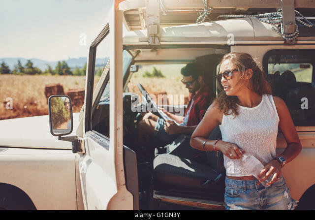 Young woman standing outside the car holding a water bottle with man sitting on driving seat looking at a the road - Stock Image