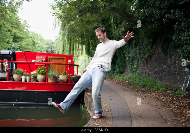 Man pretending to fall into canal , East London, UK - Stock Image
