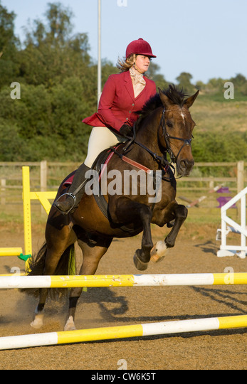 A horse and rider jumping a fence during a show jumping competition - Stock Image