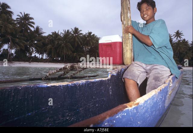 Marshallese boy on outrigger canoe - Stock Image