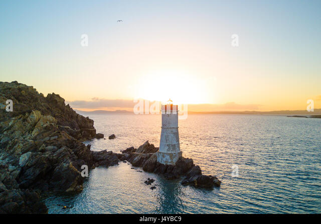Aerial view of the Italian coast at sunset With a lighthouse on the Mediterranean sea. Porto Cervo - Emerald coast, - Stock Image
