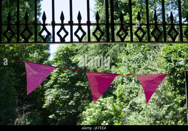 Pink bunting or 3 flags haning under and iron gate with a background of green leaves on trees lit by bright sunlight - Stock Image