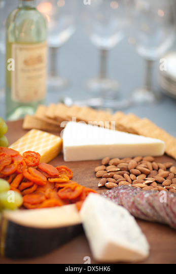 Cheese, crackers, nuts, grapes and salami on wooden cheeseboard next to white wine, close up - Stock Image