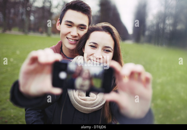 Young couple looking happy while taking pictures using a smart phone at the park. Teenage boy and girl in love photographing. - Stock Image