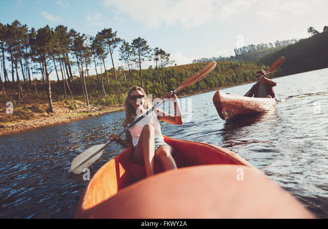 Young people kayaking on a lake. Smiling young woman kayakers with a man paddling kayak in the background. - Stock Image