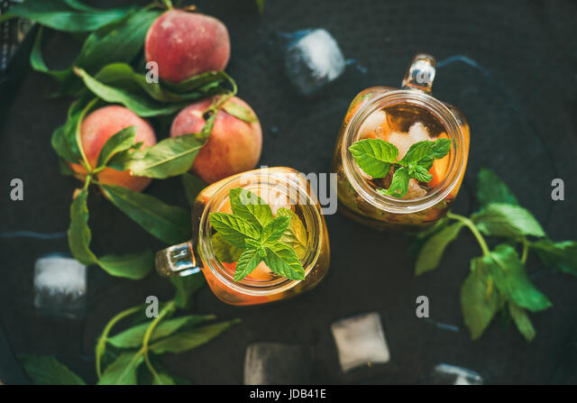 Summer refreshing cold peach ice tea in glass jars - Stock Image