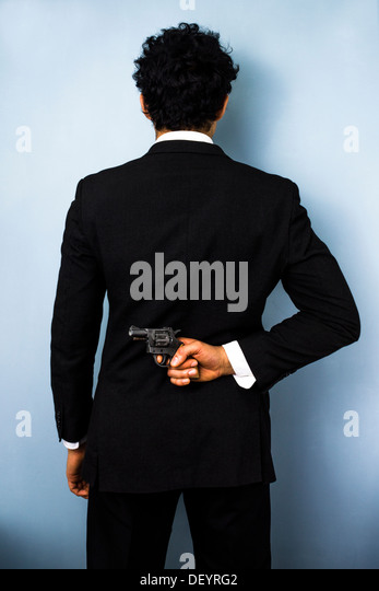 Rear view of businessman hiding a gun behind his back - Stock Image