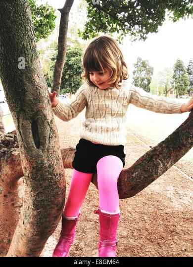 Girl (4-5) wearing pink boots climbing tree - Stock Image
