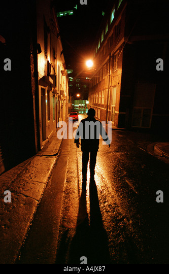 The dark shape of a man in a lonely city street at night. - Stock-Bilder
