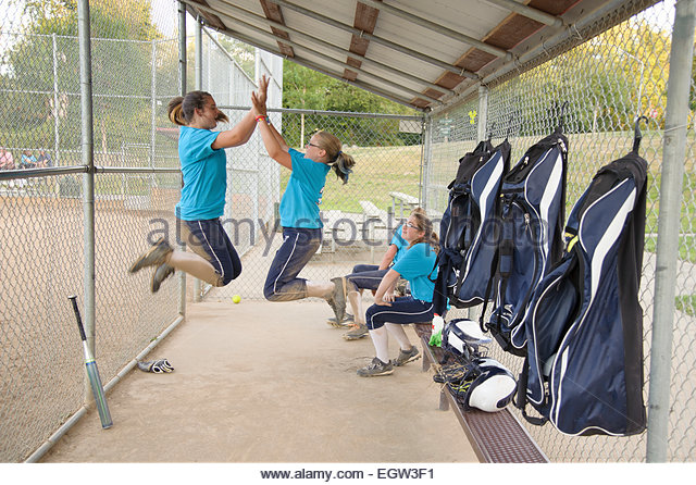 Soft ball players jumping and giving a high five. - Stock Image