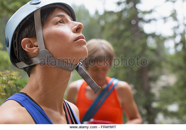 female rock climber looking up at challenge - Stock Image