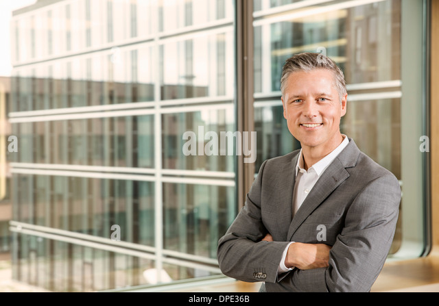 Portrait of businessman with arms crossed - Stock-Bilder