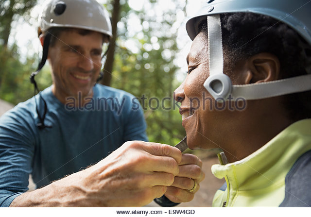 Man fastening womans rock climbing helmet - Stock Image