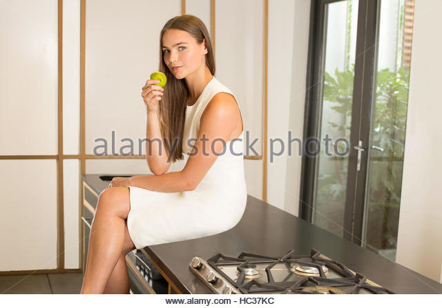 Woman sitting on kitchen surface eating apple - Stock Image