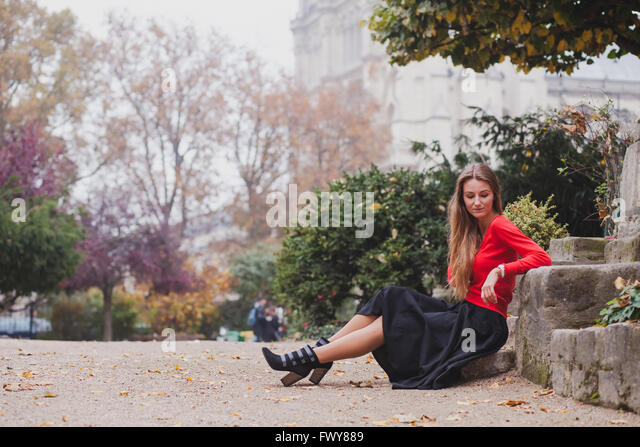 beautiful woman in red, portrait of caucasian fashion young model with long hair sitting alone, psychology concept - Stock Image