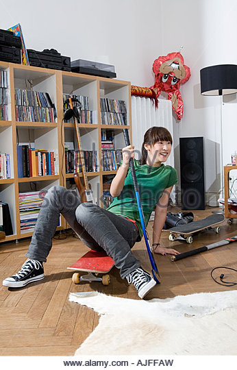 Woman with skateboard and hockey stick - Stock Image