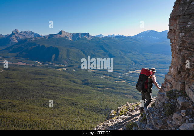 A hiker traverses a ledge, Castle Mountain, Banff National Park, Alberta, Canada. - Stock Image