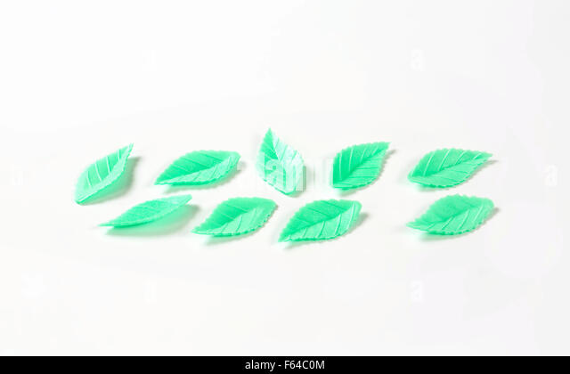 green sugar leaves - eatable cake decoration on white background - Stock Image
