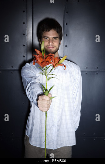 Young man holding flowers - Stock Image