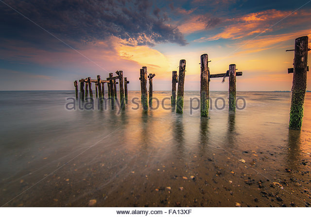 Colorful scene of wood pilings at Walnut Beach in Stratford Connecticut at the beach shore at sunset - Stock Image