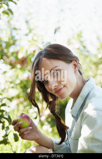 A young woman holding a freshly picked apple from the tree - Stock Image