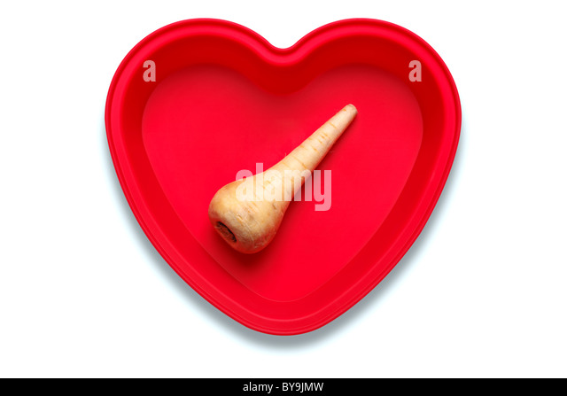 Conceptual photo of a parsnip in a heart shaped dish to represent a love of the vegetable, isolated on a white background - Stock Image