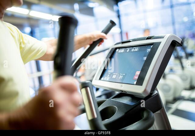 PROPERTY RELEASED. MODEL RELEASED. Man exercising on exercise treadmill in gym. - Stock Image