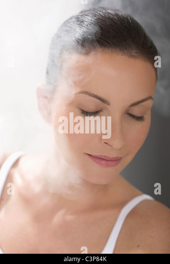 Woman relaxing in steam bath, eyes closed, portrait, close-up - Stock Image