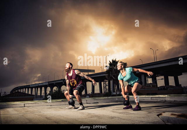 Man and woman training with kettlebells on gymnasium rooftop - Stock Image