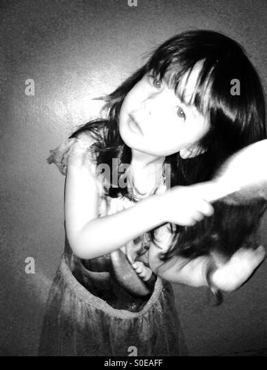 3-year old girl brushing her long hair - Stock Image