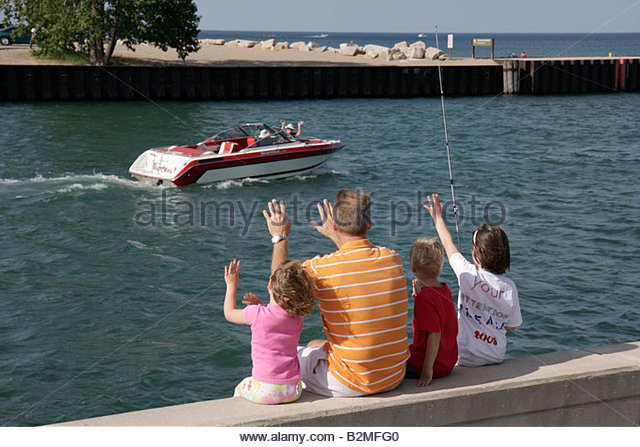 Wisconsin Kenosha Lake Michigan Harbor Park man girl parent child family fishing outdoor activity boat wave - Stock Image