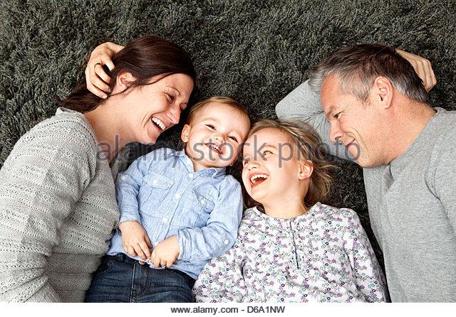 Family smiling together on carpet - Stock-Bilder