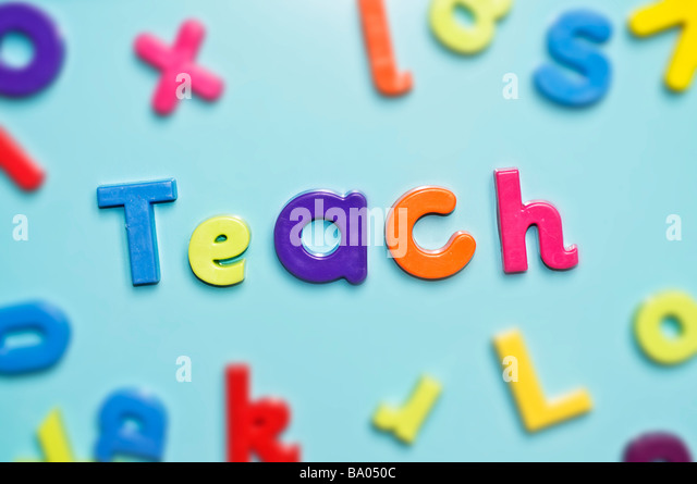 Magnetic alphabet letters spelling teach word - Stock Image