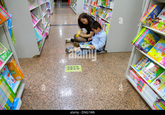 Beijing China Wangfujing Xinhua Bookstore shopping inside sale books shelves Asian woman mother boy son family browsing - Stock Image