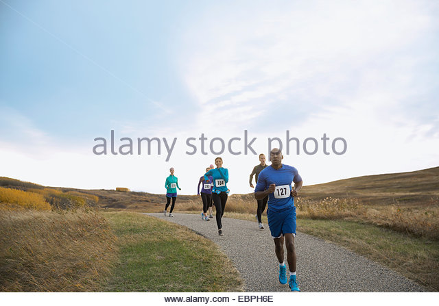 Runners racing on rural path - Stock Image