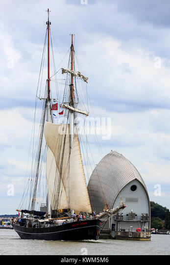Top sail schooner Wylde Swan passes the Thames Barrier on the River Thames on the first day of the Tall Ships Festival - Stock Image