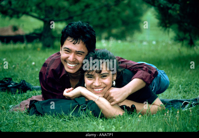 New Jersey Paramus Hispanic couple students lie in grass romantic laugh relationship romance - Stock Image