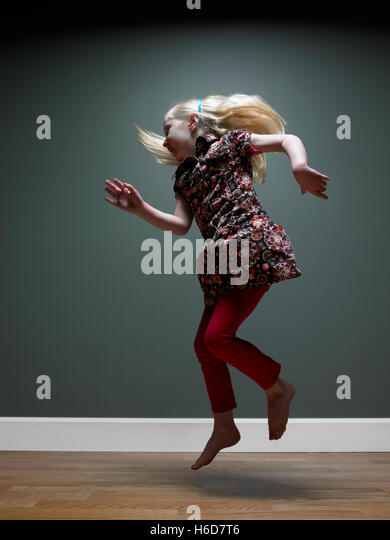 Girl jumping (3-5), studio shot - Stock Image